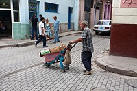 Cuba, Havana Vieja, man pushing Saint in cart