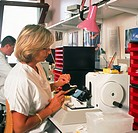 Histology laboratory. Female researcher operates a microtome cutting device in an histology laboratory. Using forceps and a brush she removes wax cutt...