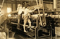 Child labour in America. Boys working in a spinning room at Bibb Mill No. 1, Macon, Georgia, USA. They are so small they have to climb up on the spinn...