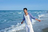 Mediterranean latin young man on summer blue beach wakling relaxed