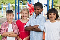 Group of children on a school playground smiling and looking at camera.