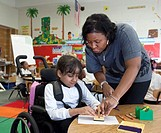 Detroit, Michigan - A teacher helps a girl in a wheelchair in a classroom at Oakman Elementary school  Teachers and para-professionals at the school a...