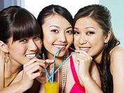 Three young women sharing orange juice