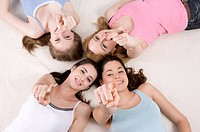 Four women lying in circle pointing at camera