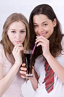 Two young women sharing a glass of drink