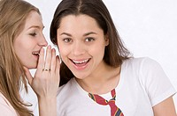 Young woman whispering to friend