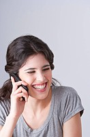 Young woman laughing happily on the phone