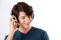 Young man listening to music with headphones, smiling