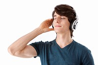 Young man listening to music with headphones, eyes closed