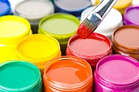 A paintbrush and jars of paint in different color