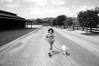 Girl running with dog down long driveway