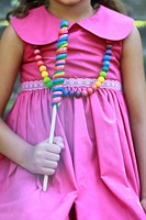Girl in magenta dress holding lollipop