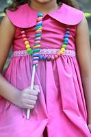Girl in magenta dress holding lollipop