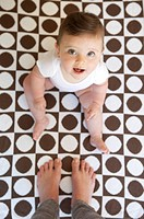 Smiling baby on geometric patterned blanket