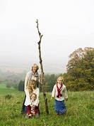 Germany, Baden_Württemberg, Swabian mountains, grandmother with granddaughters in landscape, holding branch