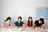 Four students sitting in classroom, writing