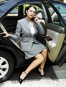 A youngbusiness woman getting out of the car, talking on the phone