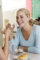 Young woman sitting with friend in cafe (thumbnail)
