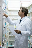 Pharmacist checking shelf for medication