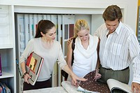 Woman assisting couple choosing wallpaper samples in store