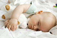 Infant sleeping with stuffed toy