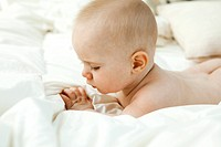 Baby lying on bed, looking at fingers