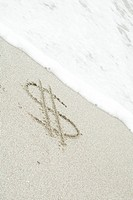 Dollar sign drawn in sand at the beach