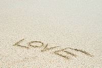 The word love written in sand at the beach
