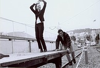 Young woman standing on a trolley being pushed by a young man on a railroad track