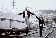 Young man standing on a trolley and holding hands of a young woman on a railroad track