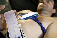 Doctor performing portable EKG electrocardiogram on patient