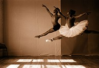 Male and female ballet dancers jumping in a studio