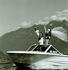 Young couple exclaiming with joy on the speedboat