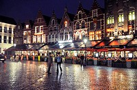 Rainy night in Bruges Brugge  City square with neon lights reflections on the brick streets
