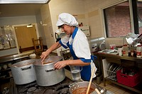 School cook preparing dinner in a primary school kitchen, UK