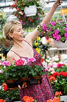 Woman choosing summer flowers in a greenhouse