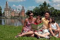 FAMILY ON THE PARK´S LAWN READING AND PLAYING THE GAMES IN A GUIDE BOOK ON THE HISTORY OF THE CHATEAU DE MAINTENON, EURE_ET_LOIR 28, FRANCE
