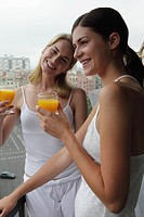 A smiling lesbian couple having orange juice at balcony