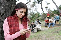 Young stylish woman texting on phone outdoors.