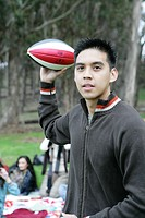 Young man throwing football outdoors.