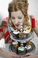 Beautiful young woman with cupcakes in foreground