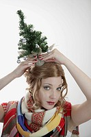 Close_up of beautiful young woman holding Christmas tree