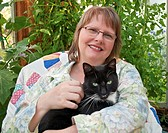 This middle aged woman is smilling and happy as she's holding a black cat with green eyes in a greenhouse She's wearing glasses and in a peaceful them...