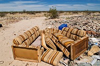 discarded couch sits in sun as desert of Northern Baja California serves as trash dump for nearby residents, South of San Felipe, Baja California, Mex...