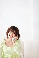 Young woman using phone, smiling, copy space