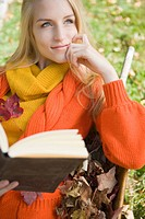 Portrait of young blonde woman holding book outdoors on autumn day