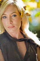 Close_up of serious blonde woman with leaves in hair
