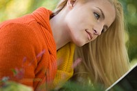 Close_up portrait of young blonde woman reading outdoors