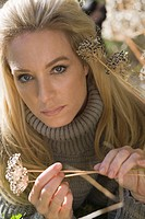Close_up of young woman in grey turtleneck sweater outdoors