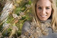 Portrait of young blonde woman in grey sweater lying on grass amidst dried flowers